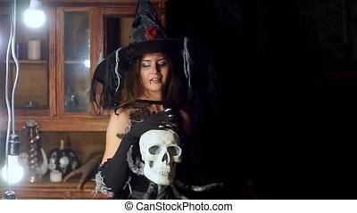 Halloween witch with a staff strokes a skull. Looking for a...