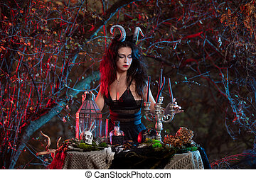 Halloween witch with horns on her head puting candles in a candlestick in the dark forest. Halloween art design