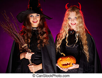 Halloween witches - Portrait of two happy females with broom...