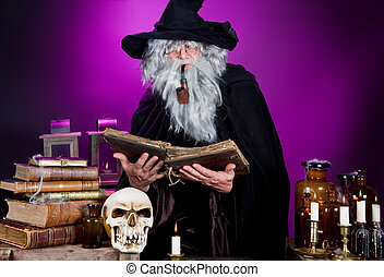 Old halloween wizard reading a spell book in his kitchen
