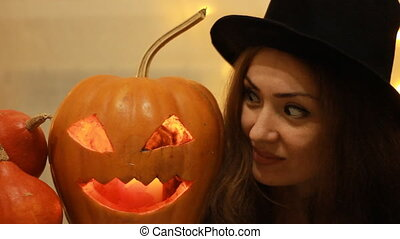 Halloween. Woman in the black hat with pumpkins. Portrait close up