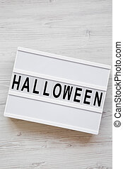 'Halloween' word on lightbox over white wooden background, overhead view. From above, top view.