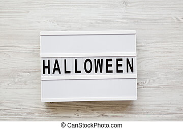 'Halloween' word on lightbox over white wooden background, top view. From above, overhead.