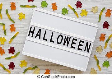 'Halloween' word on modern board, jelly monsters and worms over white wooden background, overhead view. From above, top view.