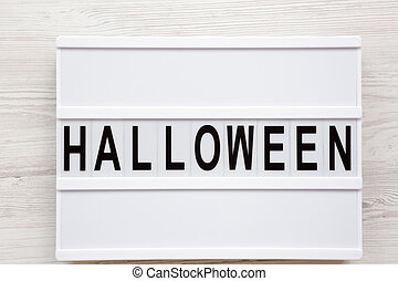 'Halloween' word on modern board over white wooden background, overhead view. From above, top view, flat lay.