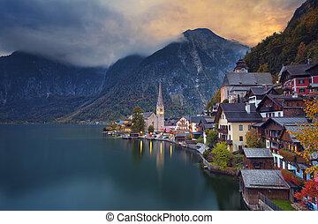 Image of famous alpine village Halstatt during colourful autumn sunset.