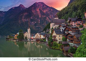Image of famous alpine village Halstatt during colourful summer sunset.