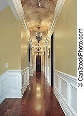 Hallway with chandeliers in luxury suburban home