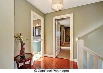 Hallway with olive walls and hardwood floor.