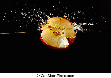 Halved apple falling into the water with a splash on a dark background closeup