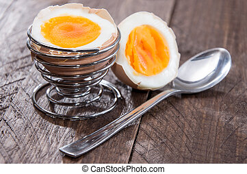 Halved egg on wooden background