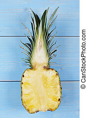 Halved pineapple on wooden table
