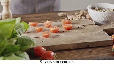 Halved red cherry tomatoes and seeds of pepper on cutting...