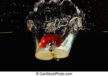 Halved ripe apple falling into the water with a splash on a ...