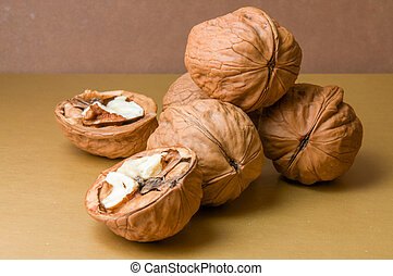 Halves and a pile of walnuts on a brown background