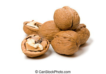 Halves and a pile of walnuts on a white blured background