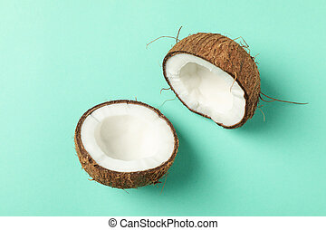 Halves of coconut on mint background, top view
