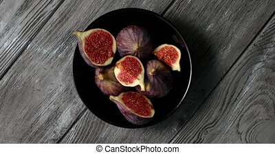 Halves of figs served on plate - From above view of black ...