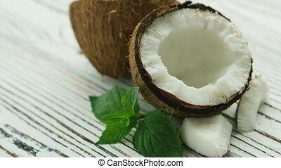 Halves of fresh coconut with mint leaves - Closeup shot of...
