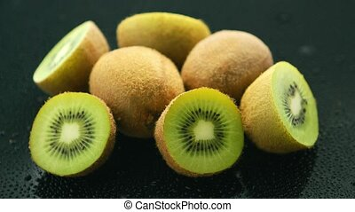 Halves of green kiwi - Closeup of pile of whole and halves...
