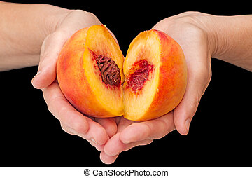 Halves of ripe peaches in the palms - Peach halves in his...
