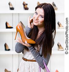 halvfigur, stående, av, kvinna, hålla, stilig, sko