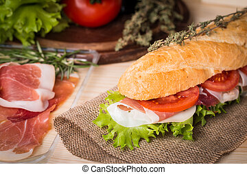 Ham and cheese salad submarine sandwich from fresh baguette on burlap