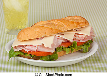 Ham and swiss cheese sub sandwich with lettuce and tomato on a bun with a drink