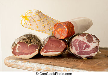 Ham and Sausage on Wooden Counter - Logs of ham or lunch...