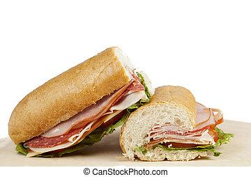 ham submarine sandwich on a cutting board over white background