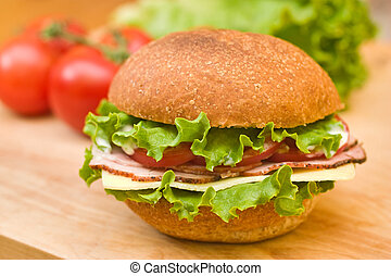 Fresh whole wheat roll with ham, swiss cheese, lettuce, tomatoes and mayo, on a cutting board with fresh vegetables in the background