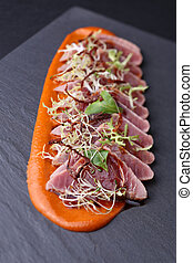 Ham with arugula, microgreen and the carrot sauce on dark...