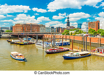 Hamburg cityscape at sunny summer day. View of the harbor with touristic boats. Popular travel destination in the northern Europe
