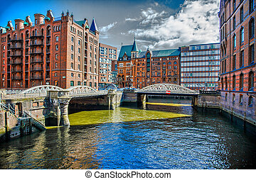 Downtown Hamburg on a cloudy day. Tourist boats passing on the waterways.
