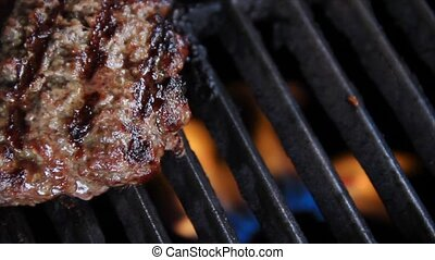 A sizzling hamburger is flipped on a flaming grill. Shot in 1920x1080p.