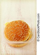 hamburger in plastic box on white wooden background