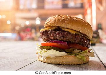 Hamburger on gray wooden surface.