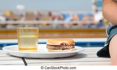 hamburger on plate near glass with juice and boy nearby