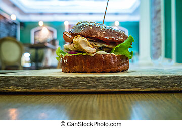 Hamburger served on cutting board over wooden table with pub interior on background