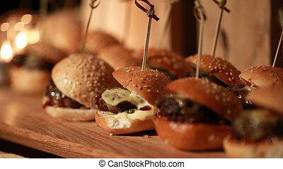 Hamburger sliders on a rustic cutting wooden board.