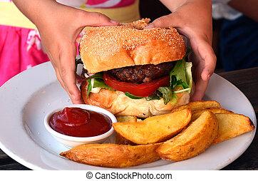 Hamburger - Hands of a little girl ready to eat a big...