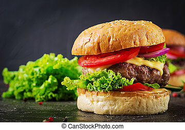 Hamburger with beef meat burger and fresh vegetables on dark background. Tasty food.