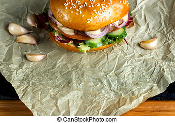 Hamburger with garlic is on kraft paper.