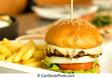 Hamburger with melted cheese and vegetable and chips