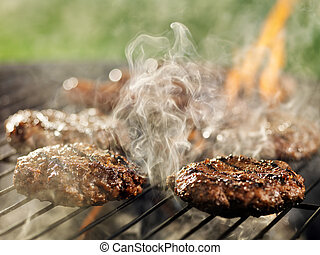 hamburgers and hotdogs with smoke and flames on grill