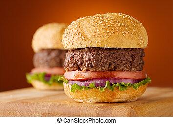 Hamburgers on wooden board on orange background.