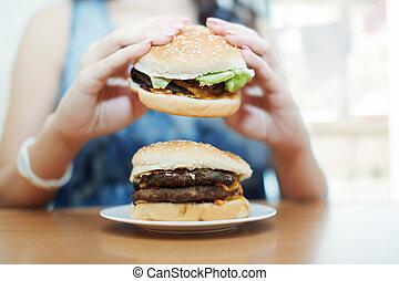 Hamburgers - Woman eating hamburgers