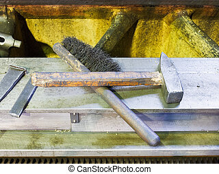 hammer and metal brush on machine frame