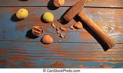 hammer and walnuts on the table , autumn and harvest