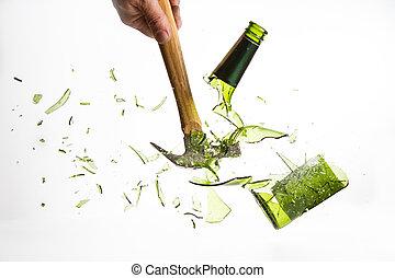 Hammer break a green glass bottle isolated on white...